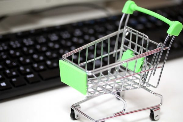 キーボードの前にショッピングカートの模型がある写真