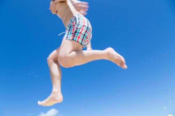 海開き 飛び跳ねてはしゃぐ 男子 写真