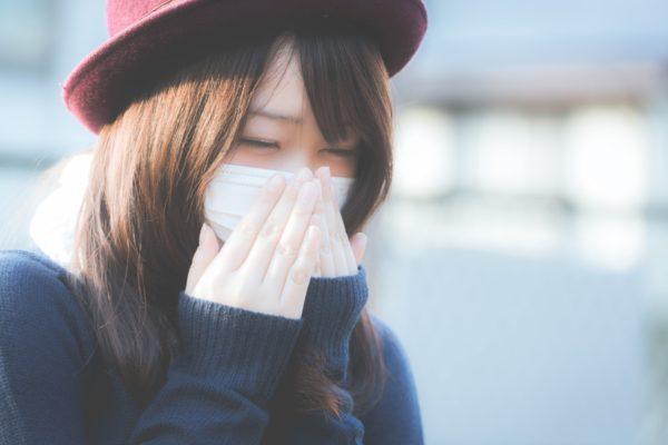 マスクを両手で押さえる女性 写真