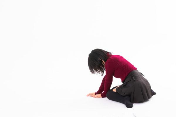 地べたに崩れる女性 写真