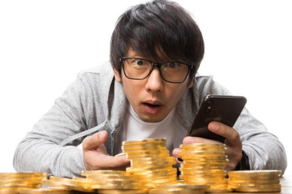 コインを積み上げる男性 写真