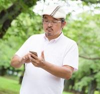 屋外でスマホ使用する男性 写真