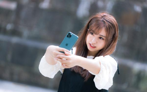 屋外で自撮りする女性 写真