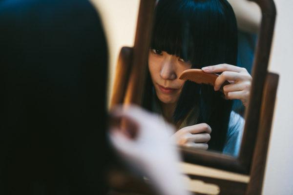 櫛で髪をとかす女性 写真