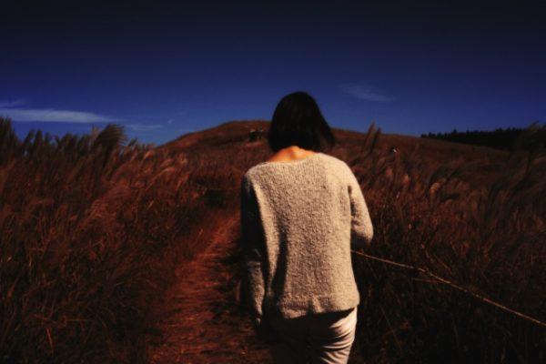 分岐点まで歩む女性 写真