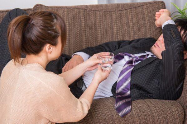 吐き気で横になる男性と心配する女性 写真