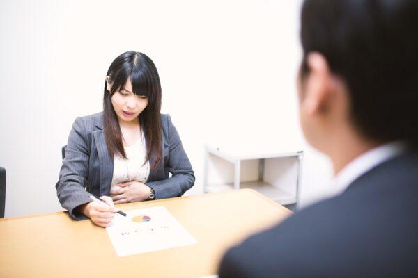 仕事中に急な腹痛に襲われる女性 写真